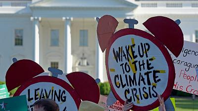 Protesters gather outside the White House in Washington, 2017, to protest President Donald Trump's decision to withdraw the Unites States from the Paris Agreement.