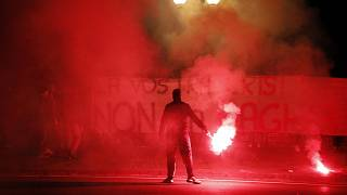 Demonstrators brandish flares and a banner during a protest against restriction measures imposed to curb the spread of COVID-19. Naples, Italy, Oct. 31, 2020