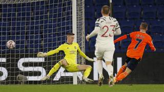 Manchester United's goalkeeper Dean Henderson, left, fails to save the ball as Basaksehir's Edin Visca, right, scores his side's second goal in the Champions League.