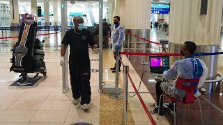 سافرون يمرون امام جهاز يقيس درجة حرارة الجسم في مطار دبي, 2020/06/10
