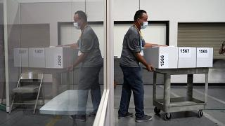 A county election worker moves boxes of counted ballots at a tabulating area at the Clark County Election Department in Las Vegas, Nevada.