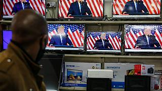 Un peatón observa la imagen de Trump repetida en las televisiones expuestas en un comercio