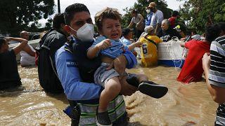 Un niño es socorrido por los equipos de rescate en Honduras