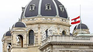 The Austrian national flag waves of half-mast on a building downtown in Vienna, Austria, Wednesday, Nov. 4, 2020.