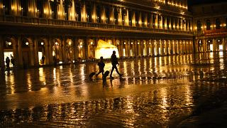 Tourists pull their luggage as they walk through a nearly empty St. Mark's Square on a rainy day in Venice, Monday, March 2, 2020
