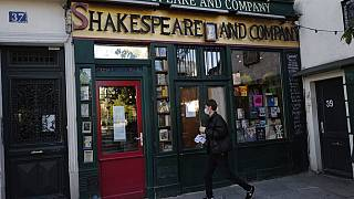A man walks by the closed English and American literature Shakespeare and Co. bookstore in Paris, France, Thursday, Nov. 05, 2020.