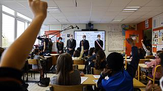 Children raise their hand as French Prime Minister Jean Castex, second left, and Education Minister Jean-Michel Blanquer, second right, attend a homage to Samuel Paty.