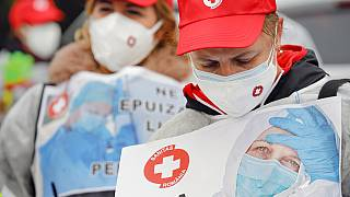 """Health care workers demonstrate in """"eshaustion protest"""" in Romania's capital."""