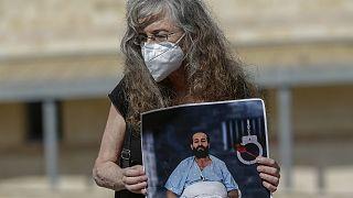İsrail'in idari tutukluluk kararına tepki için 103 gündür açlık grevinde olan Filistinli tutuklu Mahir el Ahres'in fotoğrafını tutan bir aktivist