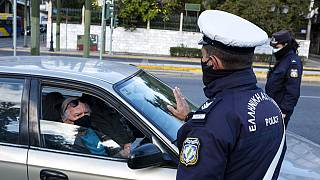 A policeman, wearing a face mask to protect against coronavirus, asks a passenger of a car to display his movement permission form