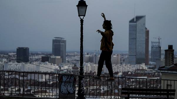 A woman balances on a railing on a hill above Lyon, France, which is in a monthlong partial lockdown