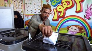 A man casts his ballot at a polling station in El-Ayyat, south of the Egyptian capital on October 24, 2020