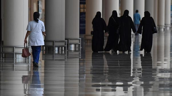Emirati women walk in a nearly deserted shopping centre during the novel coronavirus pandemic crisis in the Gulf Emirate of Dubai, on April 19, 2020.