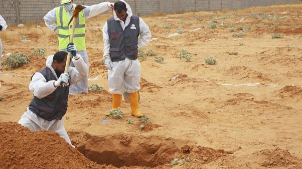 Libyan Ministry of justice employees dig out at a siyte of a suspected mass grave in the town of Tarhouna, Libya, Tuesday, June 23, 2020.