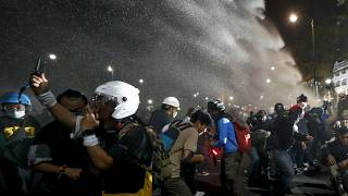 Police use water cannons to disperse pro-democracy protesters during a street march in Bangkok, Thailand Sunday, Nov. 8, 2020.