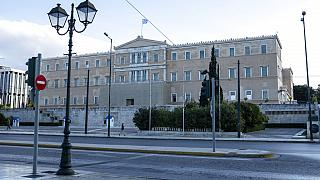 A woman walks in front of the Greek parliamen