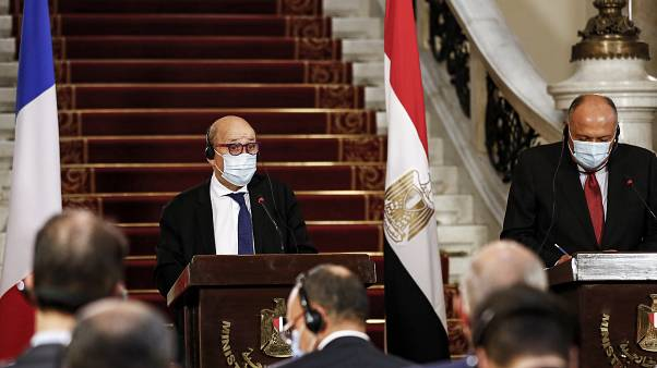 France's Minister of Europe and Foreign Affairs Jean-Yves Le Drian (L) and Egyptian Foreign Minister Sameh Shoukry (R), mask-clad due to the COVID-19 coronavirus pandemic