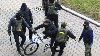 Ein Demonstrant in Minsk wird am Sonntag von maskierten Sicherheitskräften in die Zange genommen