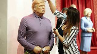 A member of the Madame Tussauds studios team places a set of golf clubs next to a wax figure of US President Donald Trump which has been re-dressed in golf wear.