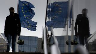 A man carries a cycling helmet as he walks by EU flags outside EU headquarters in Brussels, Wednesday, Oct. 28, 2020.