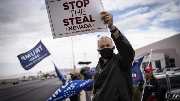 Supporters of President Donald Trump hold signs as they stand outside of the Clark County Elections Department in North Las Vegas, Nev. Saturday, Nov. 7, 2020.