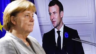 German Chancellor Angela Merkel listens to French president Emmanuel Macron, on the screen, during a virtual news conference with European leaders on terrorism