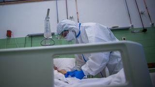 Ápoló védőfelszerelésben egy beteg pulzusát méri