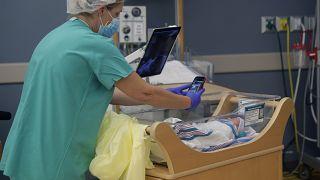 Медсестра фотографирует новорождённого для изолированной из-за Covid-19 матери