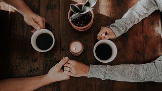 Una pareja se agarra de la mano con dos tazas de café