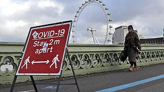 A woman walks over Westminster Bridge during the second coronavirus lockdown in London, Tuesday, Nov. 10, 2020