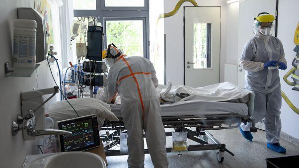 Védőfelszerelést viselő orvos és ápoló ellát egy beteget a koronavírussal fertőzött betegek fogadására kialakított osztályon