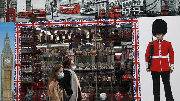 Shoppers walk past a shop window in Oxford Street, London, Tuesday, Oct. 13, 2020.