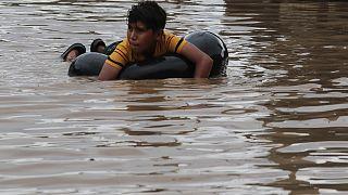 Un niño se tumba sobre un neumático hinchado en una calle inundada de Planeta, en Honduras