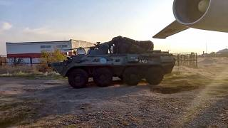 Russian military vehicle rolls past a military cargo plane at an airport outside Yerevan, Armenia.