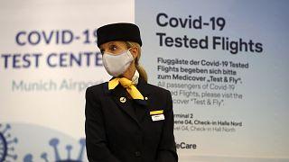 Una azafata se para frente a la entrada de un nuevo centro de pruebas rápidas de coronavirus de Lufthansa en el aeropuerto de Múnich.