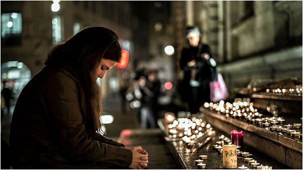 صورة لسيدة تصلي لأرواح ضحايا الهجوم عام 2015