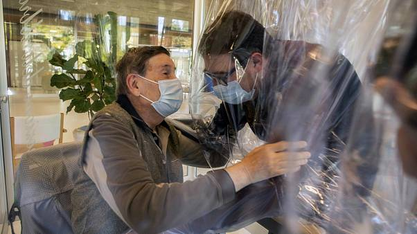 Relatives at a nursing home in Italy hug each other through a plastic film screen to avoid contracting COVID-19