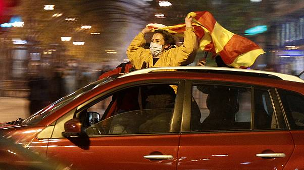 People drive cars and wave national flags celebrating the nation's qualification for EURO 2020, in a street in Skopje, North Macedonia, late Thursday, Nov. 12, 202O.