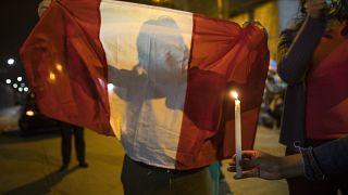 Una manifestante contra el Gobierno sujeta una bandera peruana