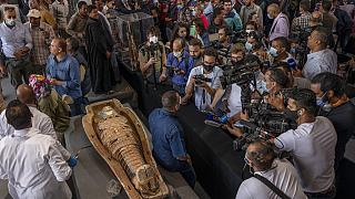 Journalists gather around an ancient sarcophagus more than 2500 years old, discovered in a vast necropolis.