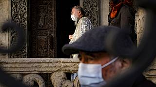 A priest wearing a mask for protection against the COVID-19 infection stands outside the Stavropoleos church, built in 1724, in Bucharest, Romania, Sunday, Nov. 8, 2020