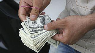 شمارش اسکناسهای دلار توسز یک فروشنده ارز در بازار تهران