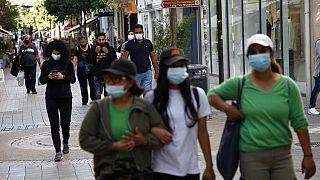 People wearing masks walk along Ledra street, a main shopping street in down town Nicosia