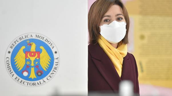 Presidential candidate Maia Sandu wearing a face mask walks to cast her ballot at a polling station during the second round of Moldova's presidential election in Chisinau.