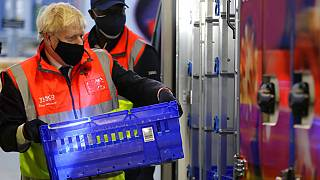 Britain's Prime Minister Boris Johnson loads a delivery van with a basket of shopping during a visit to a tesco.com distribution centre in London, Wednesday, Nov. 11, 2020.