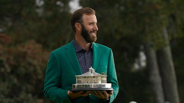 Dustin Johnson, trophée en mains et veste verte sur les épaules