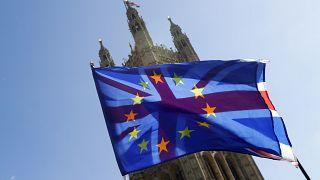 علم الاتحاد البريطاني خلف علم الاتحاد الأوروبي، على خلفية البرلمان في لندن