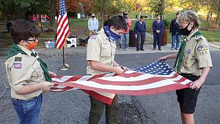 """أعضاء من الكشافة يقومون بتقطيع العلم قبل حرقه كجزء من تقليد كشفي لـ""""تقاعد العلم"""""""