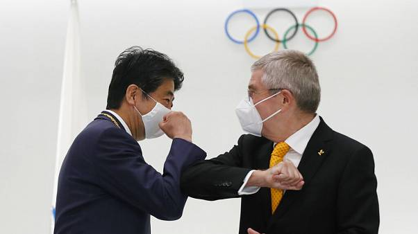 Former Japan's Prime Minister Shinzo Abe, left, and Thomas Bach, President of the International Olympic Committee (IOC), bump elbows in Tokyo