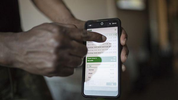 رجل يشير إلى مواعيد الصلاة على شاشة هاتفه المحمول في مارسيليا الفرنسية